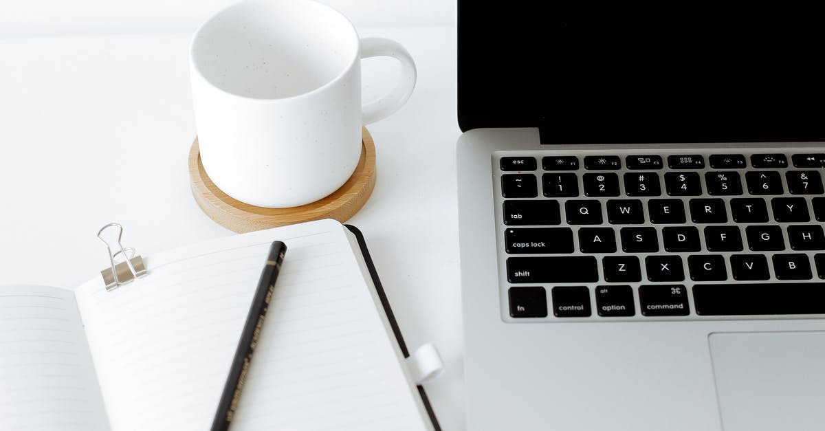 A laptop computer sitting on top of a coffee cup