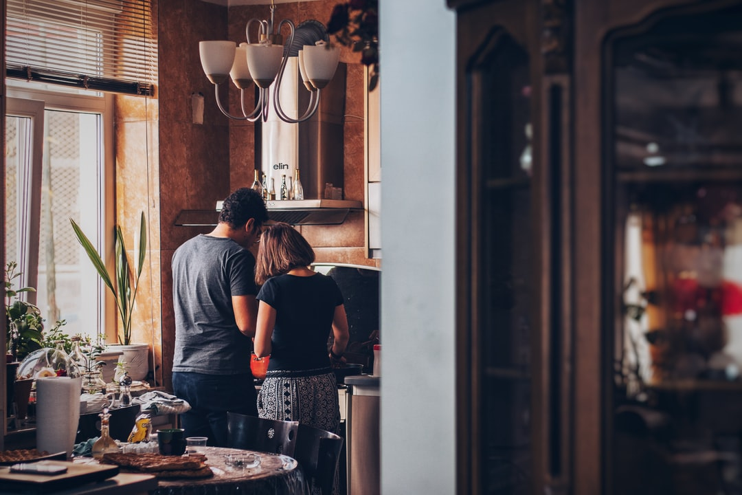 A man that is standing in the kitchen